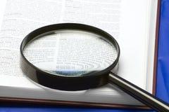Handglass su un libro Fotografie Stock Libere da Diritti