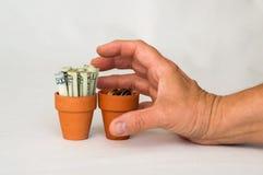 Handgrabbinpengar i en terrakottakruka Arkivbild