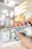 Handgreep 100 dollarrekening over onduidelijk beeld kleurrijke achtergrond Stock Afbeeldingen