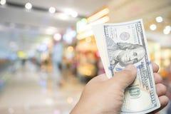 Handgreep 100 dollarrekening over onduidelijk beeld kleurrijke achtergrond Stock Foto's