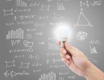 Handgreep lightbulb met uitwisselings van ideeën creatief idee op de achtergrond van de wiskundeformule Royalty-vrije Stock Foto's