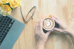 Handgriff Tasse Kaffee mit schönem Latte Stockbilder