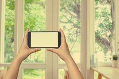 Handgriff- und -touch Screen Mobiltelefon, beweglich ?ber unscharfem Fenster mit Ansicht des Gartens stockfotografie