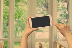 Handgriff- und -touch Screen Mobiltelefon, beweglich über unscharfem Fenster mit einer Ansicht lizenzfreies stockbild