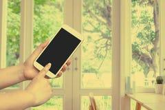 Handgriff- und -touch Screen Mobiltelefon, beweglich über unscharfem Fenster mit einer Ansicht stockbild