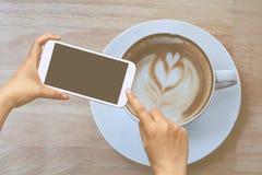 Handgriff- und -touch Screen Mobiltelefon, beweglich über unscharfem Kaffeestubehintergrund lizenzfreie stockfotos