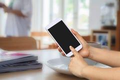 Handgriff- und -touch Screen Mobiltelefon, beweglich über unscharfem Kaffeestubehintergrund lizenzfreies stockbild