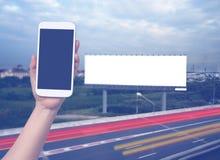 Handgriff- und -touch Screen Mobiltelefon, beweglich über unscharfem Nachtstadt scape Hintergrund stockbild
