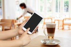Handgriff- und -touch Screen Mobiltelefon, beweglich über unscharfer Kaffeestube lizenzfreie stockfotos