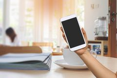 Handgriff- und -touch Screen Mobiltelefon, beweglich über unscharfer Kaffeestube stockbilder