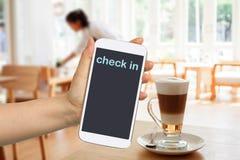 Handgriff- und -touch Screen Mobiltelefon, beweglich ?ber unscharfer Kaffeestube lizenzfreie stockbilder