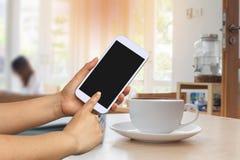 Handgriff- und -touch Screen Mobiltelefon, beweglich ?ber unscharfer Kaffeestube lizenzfreies stockfoto