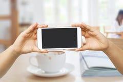 Handgriff- und -touch Screen Mobiltelefon, beweglich ?ber unscharfer Kaffeestube lizenzfreies stockbild