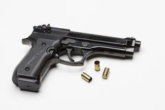 Handgun against white background with bullets, horizontal Stock Image
