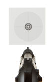 Handgun aimed on a shooting target. In the background Royalty Free Stock Photography