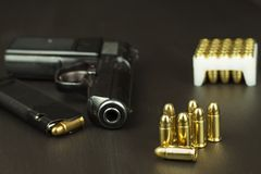 Handgun with ammunition on a dark wooden table. Sales of weapons and ammunition. Advertising on ammunition. New gun and ammunition Stock Image