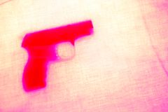 Revolver on pink background. Handgun behind pink curtain. close up. soft focus stock images