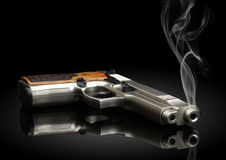 Handgun on black background with smoke Stock Images