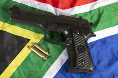 Handgun and brass bullets on a South African flag. Handgun and brass bullets on South African flag Royalty Free Stock Photo