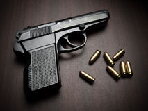 Handgun with bullets. On the wooden surface, closeup with vignette, useful for various security,protection or criminal topics Royalty Free Stock Photos