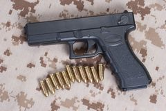 Handgun on camouflage uniform Stock Photo