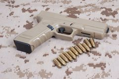 Handgun on camouflage uniform Stock Images