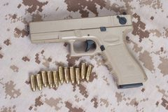 Handgun on camouflage uniform Stock Photos