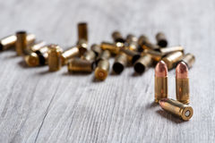 Handgun cartridges in the foreground with background of empty ca. Firearm ammunition with gunpowder and caps Royalty Free Stock Images