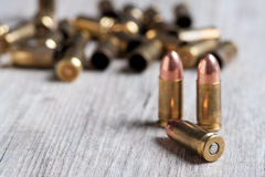 Handgun cartridges in the foreground with background of empty caps. Firearm ammunition with gunpowder and caps Royalty Free Stock Image