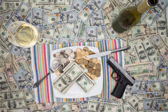 Handgun and champagne on 100 dollar bills Royalty Free Stock Photos
