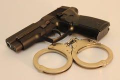 Handgun and closed handcuffs, closeup. Handgun caliber 9mm and one pair of closed handscuff, closeup view Royalty Free Stock Image