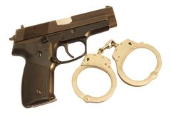 Handgun and closed handcuffs isolated Royalty Free Stock Images