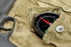 Handgun and Compass On The Weathered Backpack Stock Photos