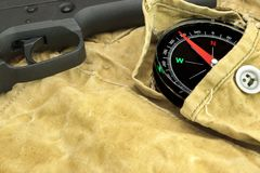 Handgun and Compass On The Weathered Backpack. Modern Handgun and Compass On The Weathered Backpack Stock Images