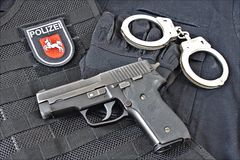 Handgun with handcuff, gloves on uniform shirt and tactical vest with patch of Niedersachsen State Police, Germany Royalty Free Stock Image