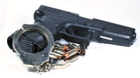 Handgun with handcuffs Stock Images