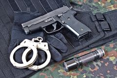 Handgun with handcuffs, gloves and flashlight on tactical vest and camouflage clothing. Handgun with handcuffs, gloves and flashlight on black tactical vest and Stock Images