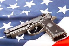 Handgun lying on satin US flag - studio shoot Royalty Free Stock Photos