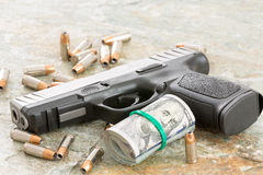 Handgun with money and scattered bullets. Conceptual image of a handgun with a roll of money surrounded by scattered bullets and cartridges on an old weathered Royalty Free Stock Image