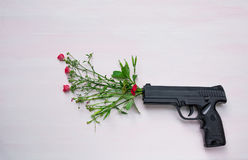 Handgun On Wooden Background With Flowers.War And Peace Royalty Free Stock Photo