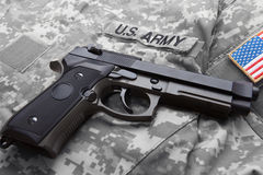 Handgun over American solder's uniform with shoulder patch on it Royalty Free Stock Images