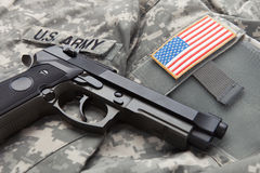 Handgun over USA solder's uniform with shoulder patch on it Royalty Free Stock Photography