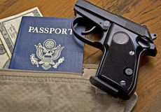 Handgun with passport and cash Royalty Free Stock Images