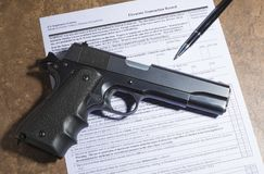 1911 handgun and pen with firearm purchase paperwork. Semi automatic 1911 handgun and pen with purchase paperwork on a tan counter Stock Image