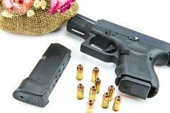 Handgun pistol and flower on white background Stock Images