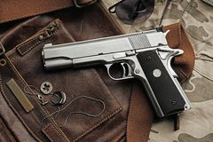 Handgun, .45 pistol. Semi-automatic handgun lying over a Leather handbag, .45 pistol stock photo