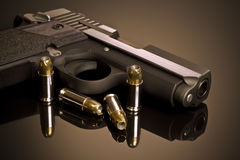 Handgun on Reflective Surface. Handgun and Hollow Point Bullets Royalty Free Stock Photo