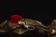 Handgun resting on a Book with a Red Rose Royalty Free Stock Photo