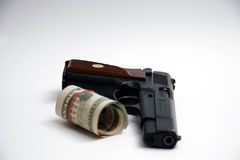 Handgun and roll of money. Modern automatic handgun with roll of dollar bills; isolated on white background Royalty Free Stock Images