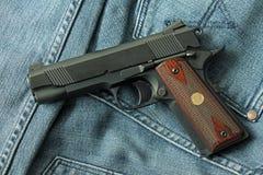 Handgun, semi-automatic. Semi-automatic handgun on blue jeans background, .45 pistol Stock Photo